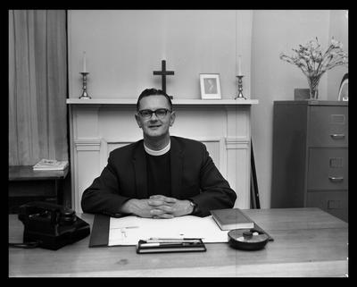 All Saints Church. Priest sitting at his desk