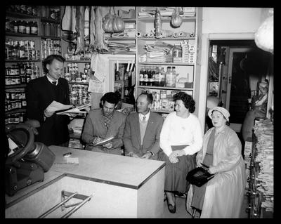 Interior of small goods shop with a group of people sitting and a man holding papers. Baltia at Argyle Street Parramatta