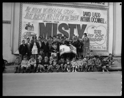 """Roxy Theatre, pony, trainer and children are standing in front of a big advertisement of film """"Misty"""""""