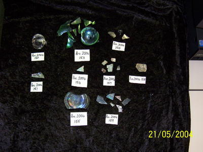 Eight (8) fragments of green glass, glazed, marked 'L C'