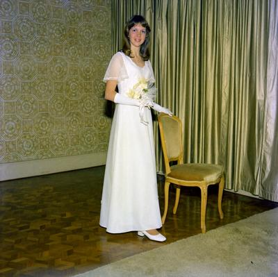 Parramatta Mayoral Ball 1976 : portrait of a debutant holding a bouquet of flowers and standing next to a chair