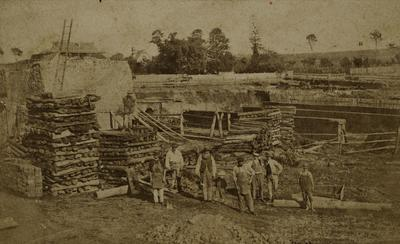 Brickworks, unknown location, view of workers, wood piles, and kiln in background, ca. 1870s - 1890s